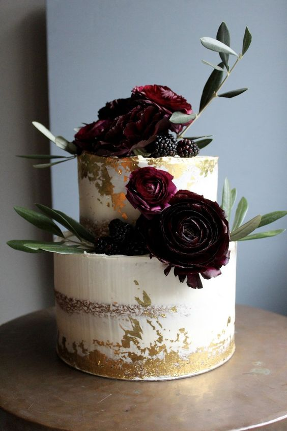 a gorgeous semi naked wedding cake with gold leaf, dark burgundy blooms, greenery and blackberries