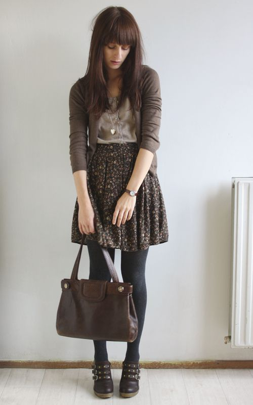 a brown floral skirt, black tights, brown booties, a neutral top and a brown cardigan for a vintage-inspired look