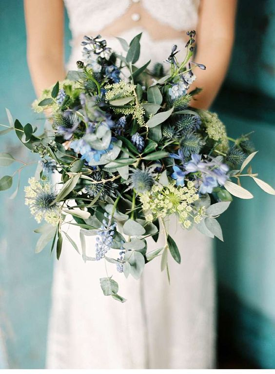 boho-inspired wedding bouquet with thistles, blue flowers and greenery of different kinds