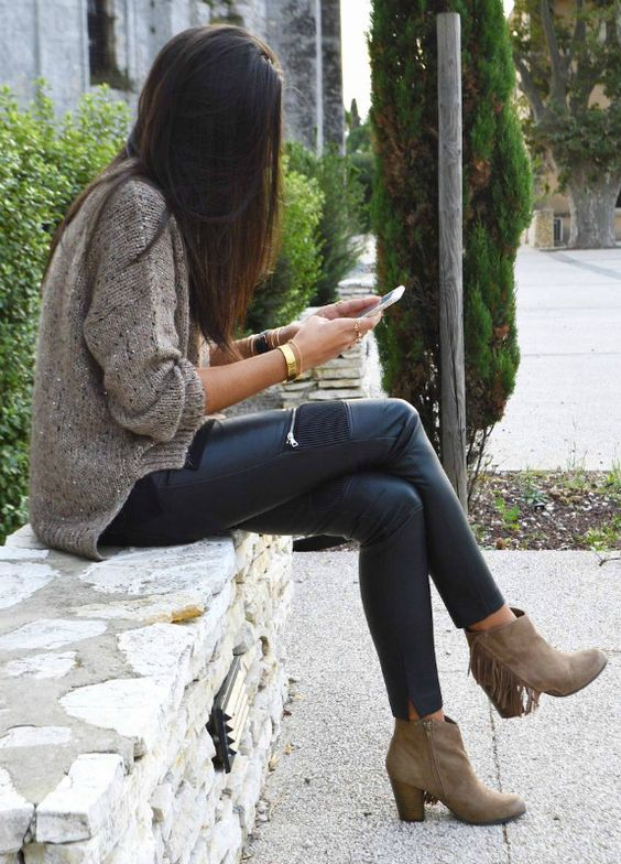 a brown sweater with a sparkle, black leather pants with zips and beige suede booties