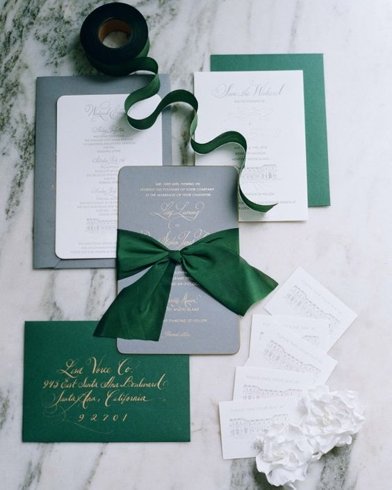grey, white and emerald invitations with gold calligraphy and large bows remind of Christmas
