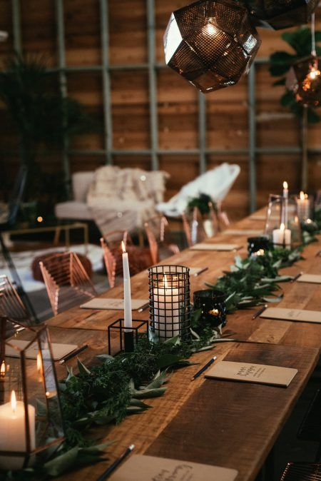 a modern greenery table runner with candle lanterns incorporated for an industrial winter wedding