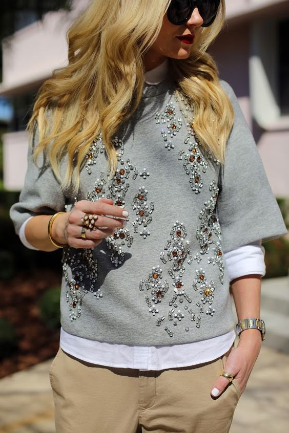 neutral pants, a white shirt and a grey embellished sweater