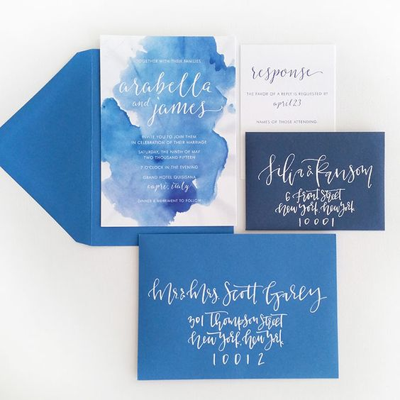 a beach wedding invitation suite with blue and navy envelopes, blue watercolor and silver calligraphy