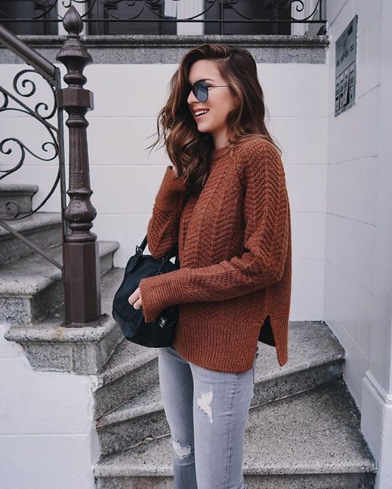 ripped grey jeans, a burnt orange sweater and a black bag