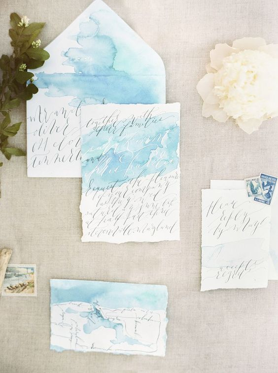 airy light blue watercolor wedding invitations with calligraphy and a raw edge for a seaside wedding