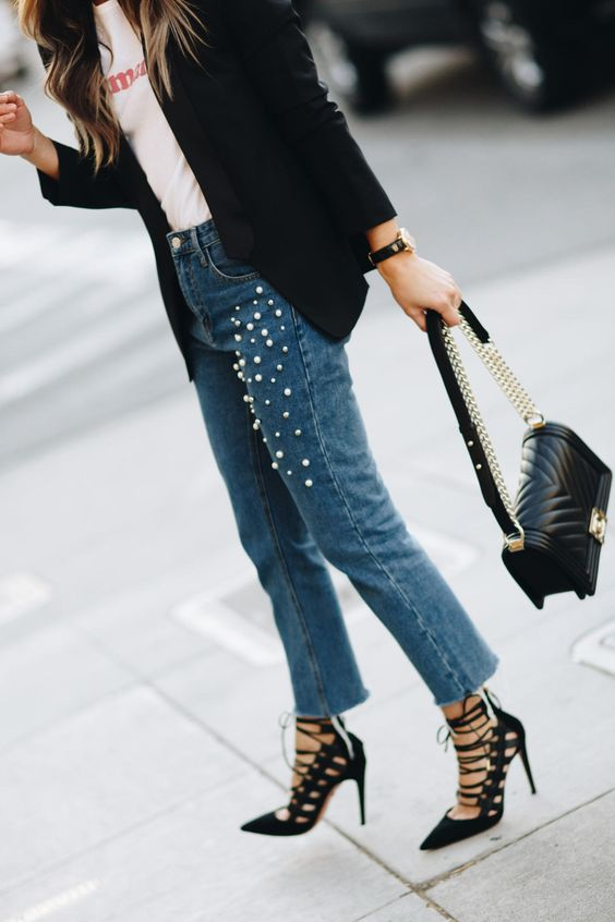 a printed tee, a black jacket, blue pearly jeans and black lace up shoes