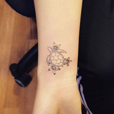 Turtle with flowers tattoo on the arm