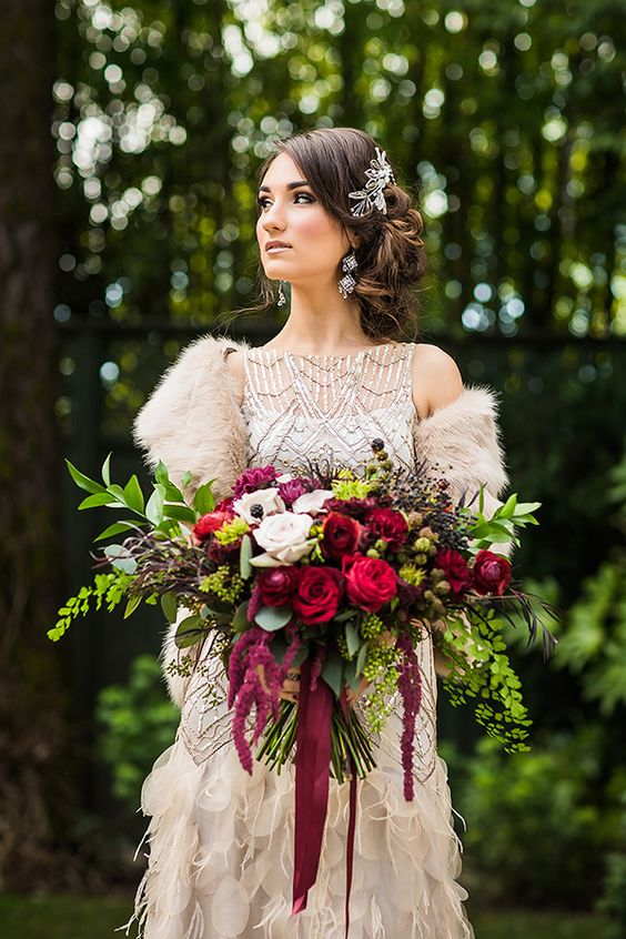 a lush and colorful winter wedding bouquet with blackberries, greenery and red and fuchsia roses