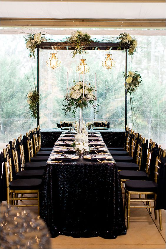 a jaw-dropping table setting with gold sequin tablecloth, gold cutlery and candle holders and black and gold chairs