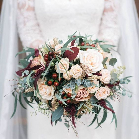 a lush bouquet with blush roses, berries, eucalyptus and bold foliage