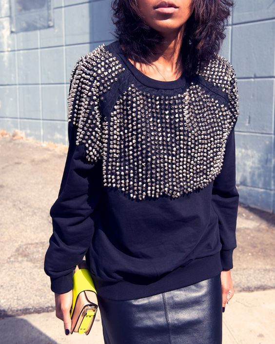a black leather skirt, a black studded sweater and a bold yellow bag