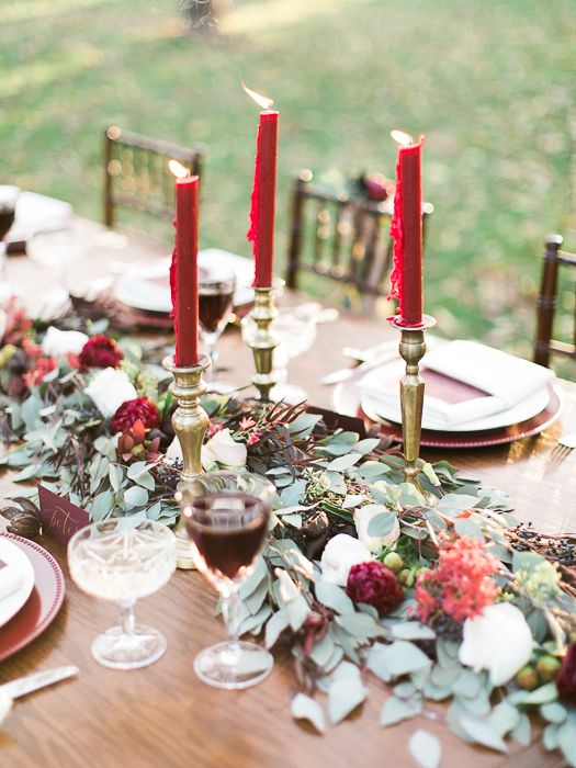 a greenery table runner with berries and plum blooms and fuchsia candles for a bold festive runner