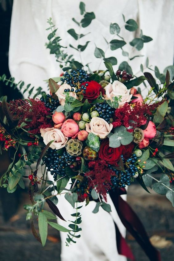 a lush textural bouquet with red roses, privet berries, eucalyptus, pink flowers and red foliage