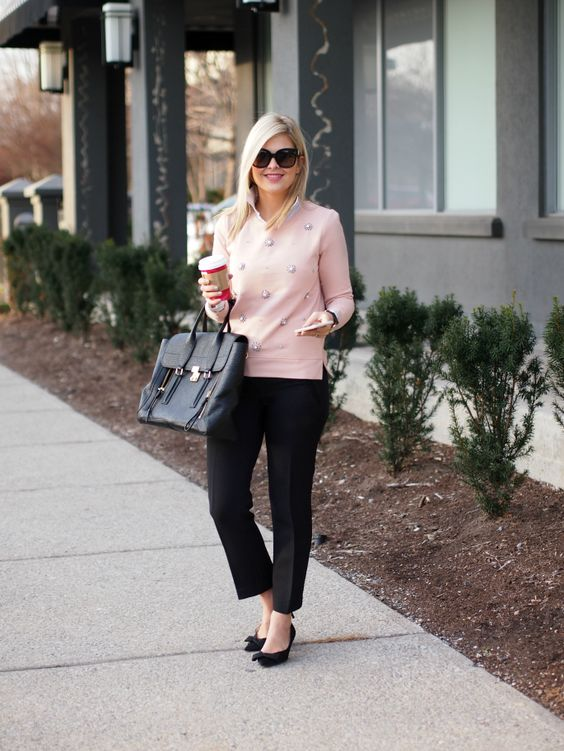 black trousers, a pink embellished sweater, black suede bow heels and a bag