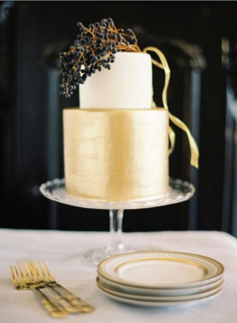 an elegant white and gold wedidng cake topped with a berry branch for a chic winter wedding