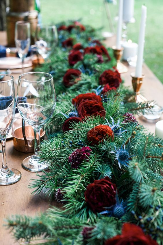 an evergreen table runner with bold burgundy blooms and thistles for a rustic winter wedding