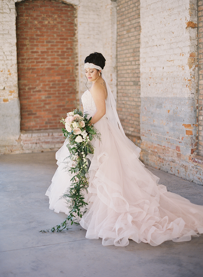 The bride was also wearing a rhinestone headpiece with ribbons and she was carrying a cascading bridal bouquet with blush blooms