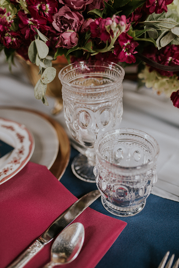vintage inspired wedding table details - http://ruffledblog.com/artist-inspired-wedding-ideas-with-oxblood-and-navy