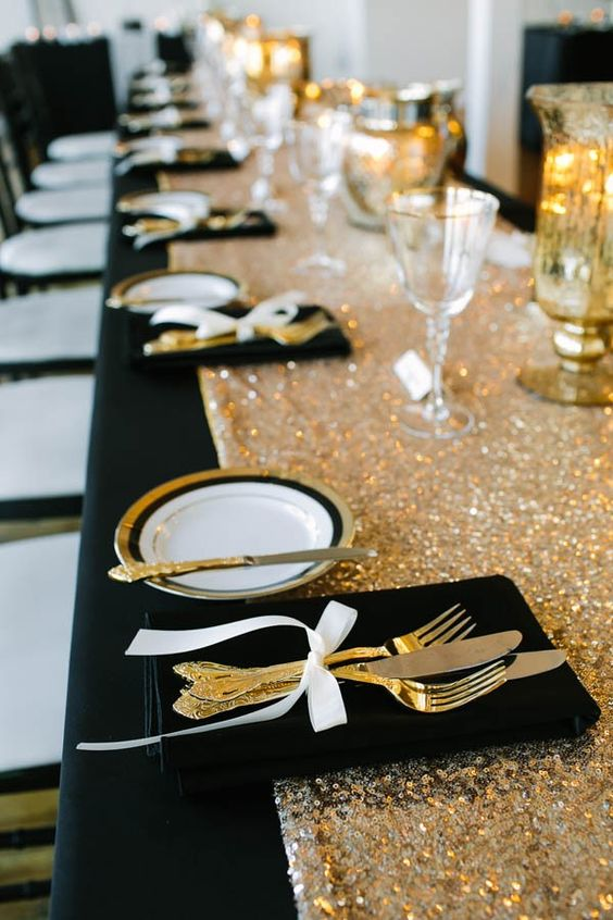 a table setting with a black tablecloth, a gold sequin table runner, gold rim plates and cutlery