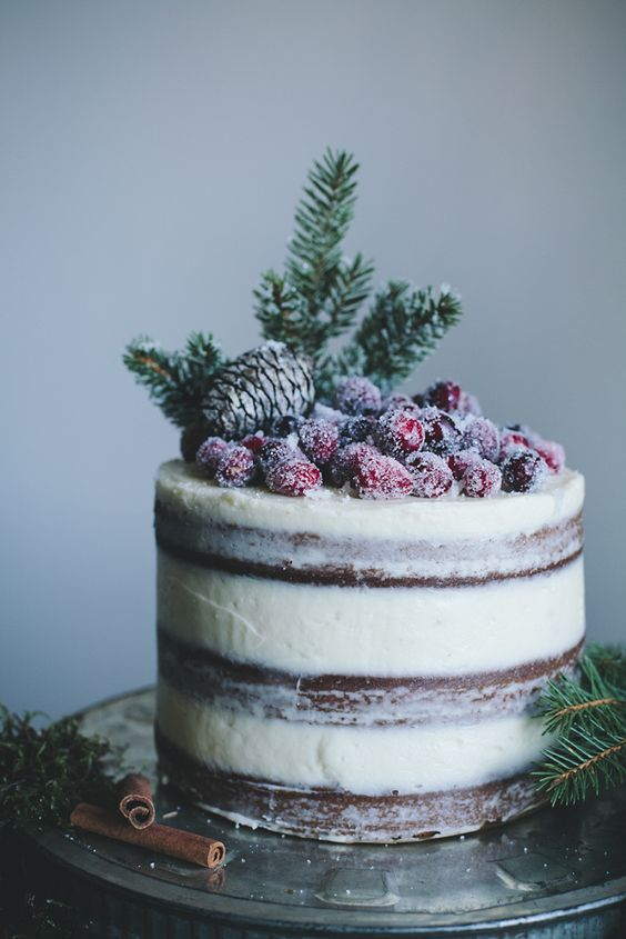 a semi naked wedding cake topped with a pinecone, evergreens and sugared berries for a winter wedding