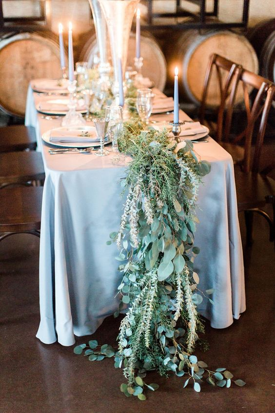 greenery and foliage table runner in pale shades looks organic with a dusty blue tablecloth