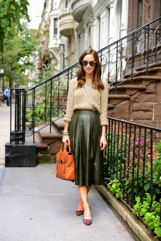 a green pleated midi leather skirt, a neutral sweater, a statement necklace and plaid heels