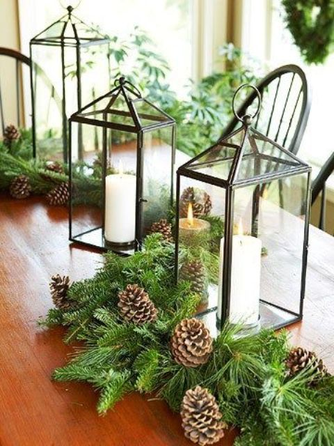 an evergreen table runner with pinecone and candle lanterns to remind everyone of winter and holidays coming