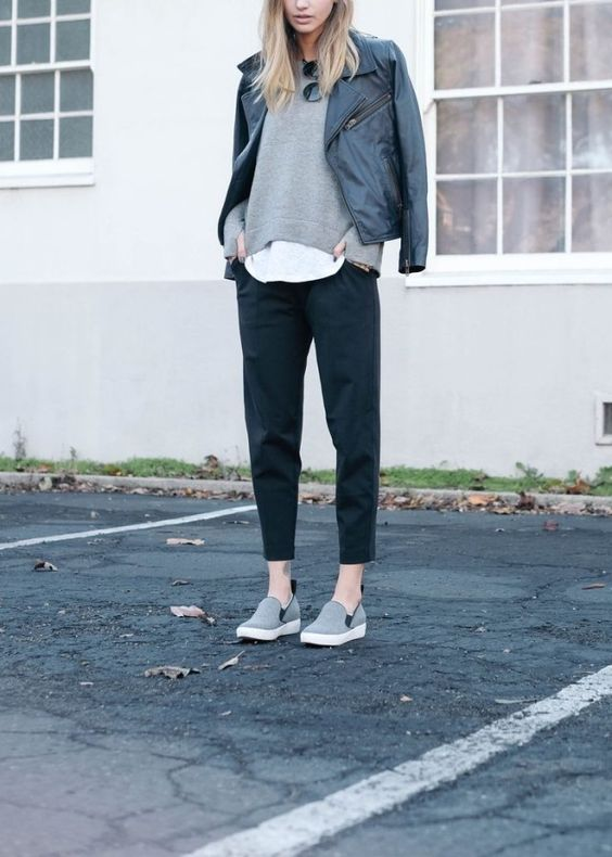 black cropped pants, a grey sweater over a top, grey flats and a black leather jacket