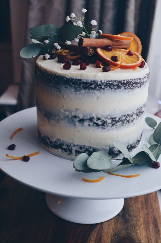 a semi naked gingerbread wedding cake with pomegranate seeds, citrus, cinnamon and flowers