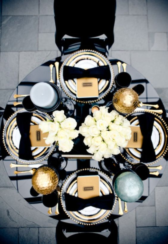 New Year's Eve tablescape with a black table, napkin bows, gold cutlery and oversized ornaments