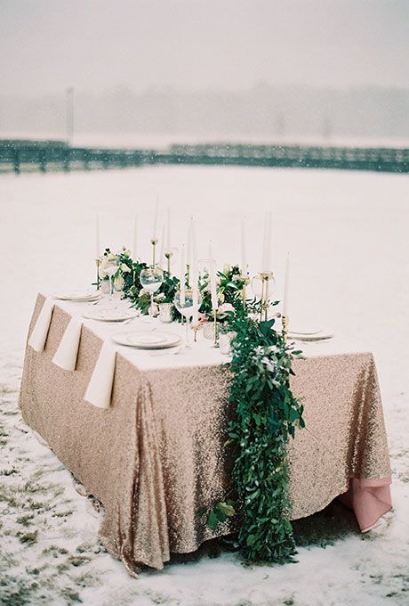 fresh greenery and white blooms table runner looks super bold on a copper tablecloth