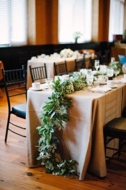 a lush cascading greenery and neutral bloom table runner for a snowy winter wedding