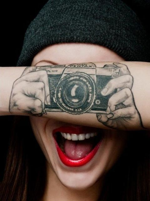 Camera and hands tattoo on the forearm