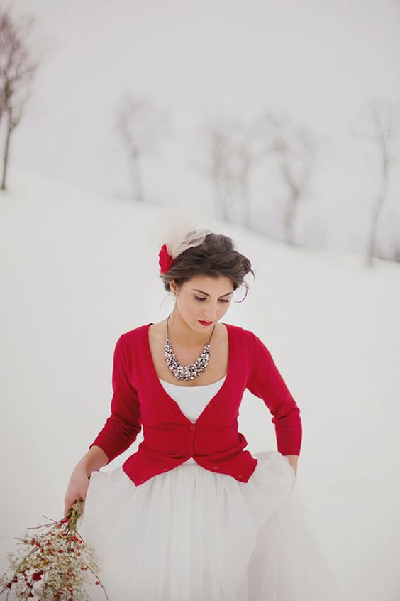 a short red cardigan and a statement necklace help to accessorize the wedding dress