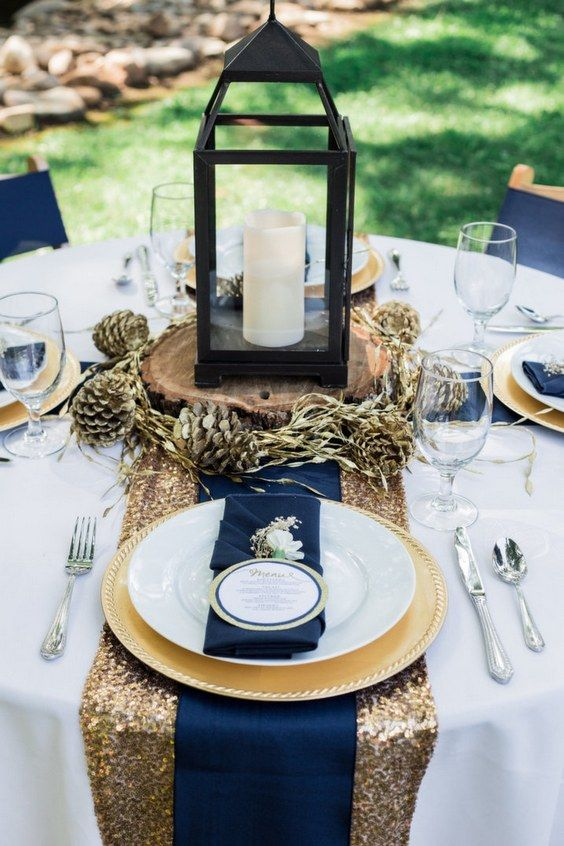 a gorgeous place setting with a gold sequin table runner, navy napkins, gilded pinecones