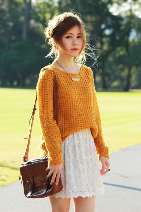 an orange sweater over a white lace dress and a brown corssbody for a cool fall look