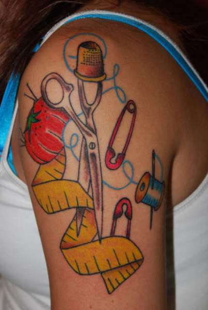 Scissors, safety pins, threads, needle tattoo on the shoulder