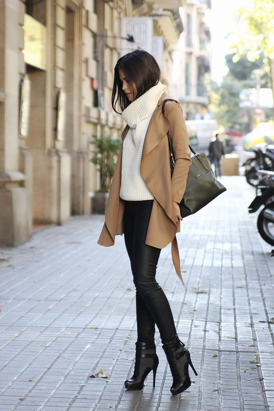 black leather pants, heeled booties, a white chunky knit sweater and a camel coat