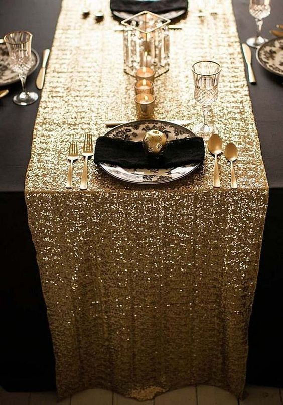 a gold sequin table runner for a black and gold wedding tablescape