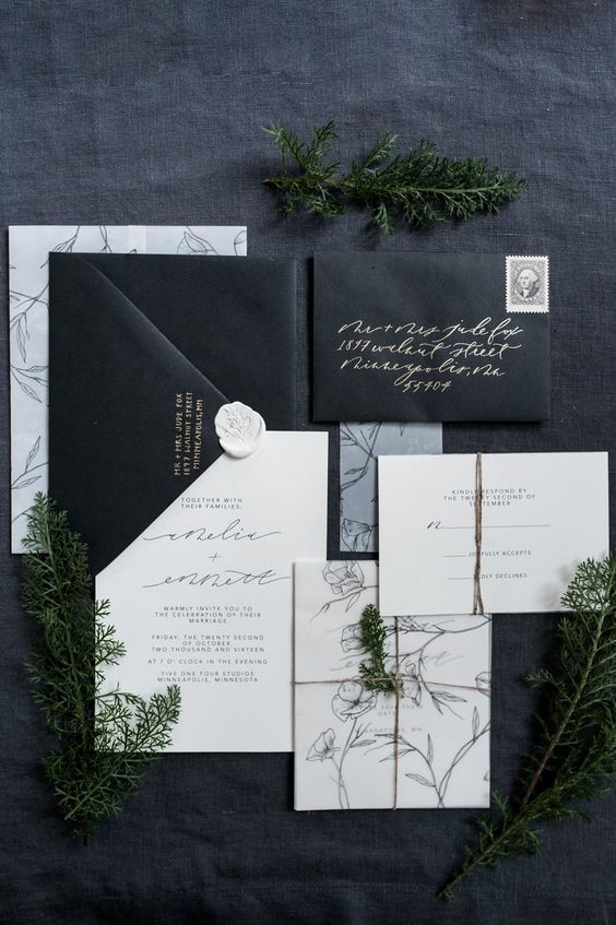 a black and white invitation suite with calligraphy and botanical silhouettes for a modern organnic wedding