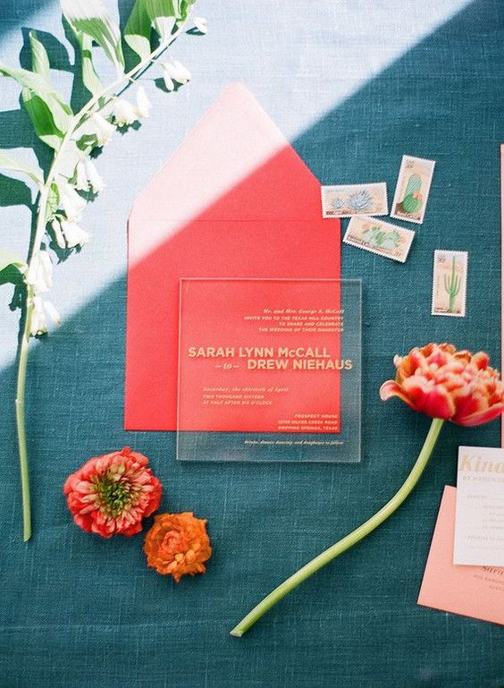 a modern acrylic wedding invitation with gold letters in a coral envelope