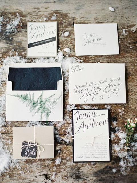 a neutral wedding invitation set with textural black lining, evergreens and black framing