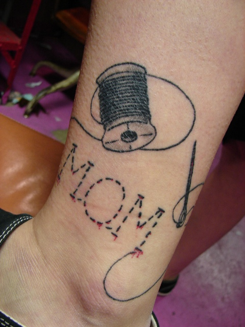 Needle and thread tattoo on the ankle