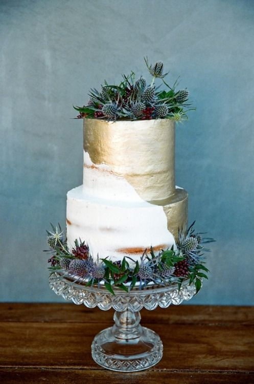 half naked, half gold leaf wedding cake with thistles and greenery for a winter celebration