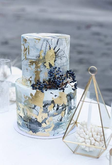 a crazy marbeleized and watercolro splash wedding cake with gold leaf and berries