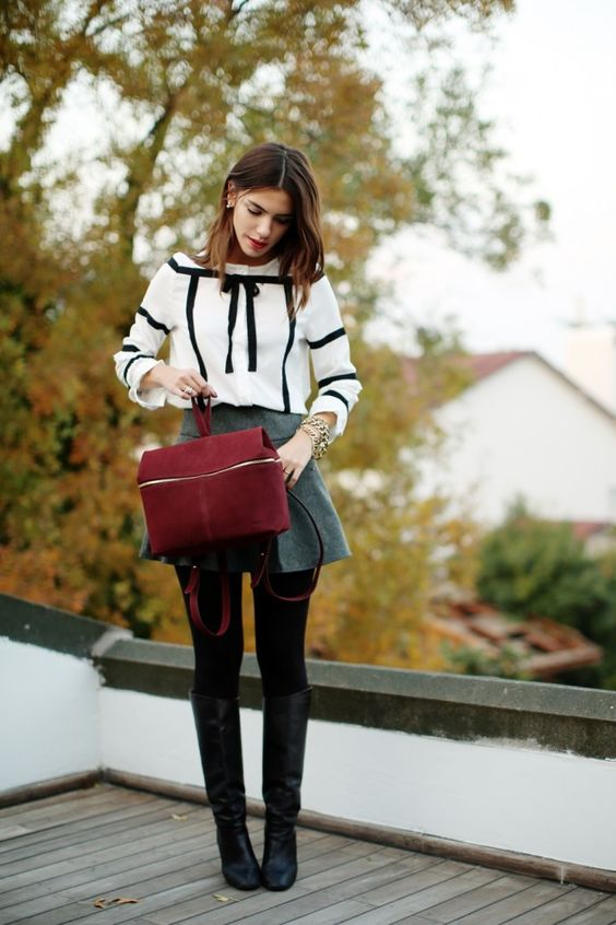 a grey A-line skirt, a white shirt with black ribbon, black tights, black tall boots and a red suede bag