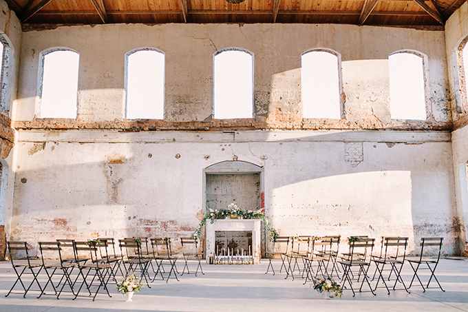 The wedding venue was done with simple industrial chairs and a faux fireplace with candles and lush greenery and blooms