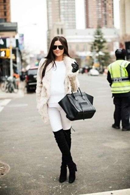 a white sweater, white leggings, black tall boots, a creamy faux fur coat and a black bag