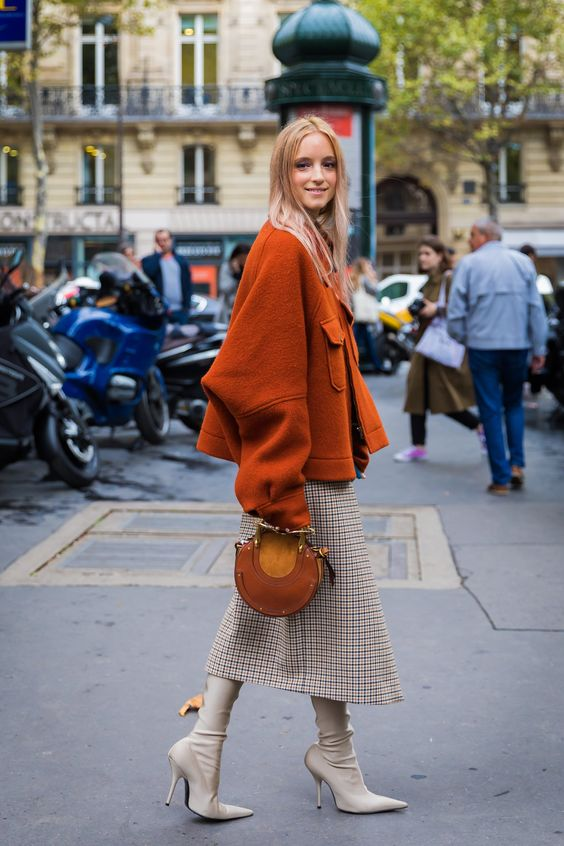 a chic slouchy cropped burnt orange coat and a matching purse, a printed midi skirt, creamy boots